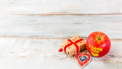 Message I love you written on a red apple. Valentine's day table place setting. Wedding background.