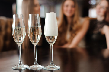 Man fills glasses of champagne for three beautiful young women