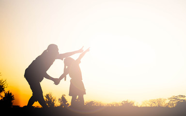 Silhouette of happy family mother and child playing outdoors at sunset Wall mural
