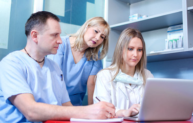 Group of three healthcare workers working together on a laptop.