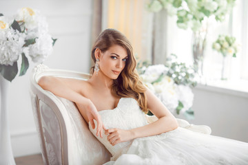 Bride in beautiful dress sitting resting on sofa indoors