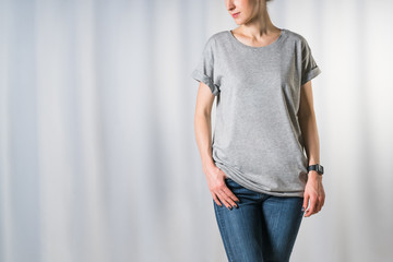 Cropped image. Front view of young woman, dressed in light gray t-shirt and blue jeans, standing on light gray background with his hand in pocket of jeans. Mock up. Space for text, advertising.