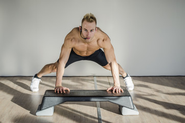 Young aerobics male coach shirtless leaning on step teaching class, looking at camera