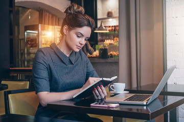 Young businesswoman in gray dress sitting at table in coffee shop and reading book. On table laptop, smartphone and cup of coffee. Student learning online. Freelancer working. Online education.