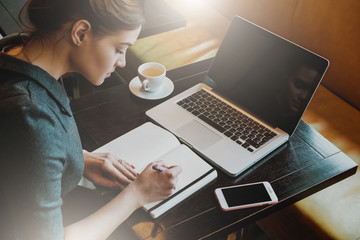 Young business woman in gray dress sitting at table in cafe and writing in notebook. On table is laptop, smartphone and cup of coffee. Freelancer working in coffee shop. Student learning online.