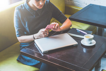 Cropped image. Young business woman sitting in cafe at table and use smartphone. On table is closed laptop, notebook and cup of coffee. Girl waiting for friends in cafe. Girl blogging, checking email.