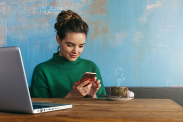 Young smiling business woman sitting at table in coffee shop and uses smartphone. On table is laptop and cup of coffee.Student learning online. Girl shopping online, checking email,blogging, chatting.