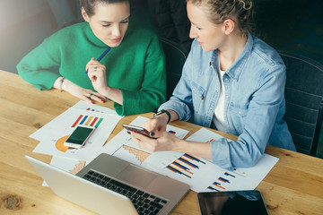 Two young business women sitting at table on which is laptop,smartphone,tablet computer,paper documents,graphics.Girl shows colleague information on your smartphone. Students learning online, working.