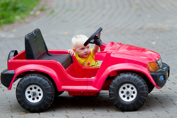 Little baby exploring toy car