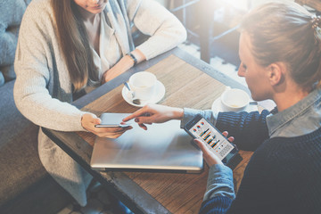 Top view of two young business women sitting at table and discussing business plan. Women using smartphones. On wooden table closed laptop and cups of coffee. Girl shows finger on screen of phone.
