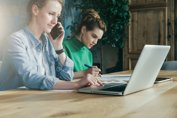 Two young business women sitting in office at table and work together.On table laptop and paper charts.First woman signs documents,second using laptop and talking on phone. Students learning online.