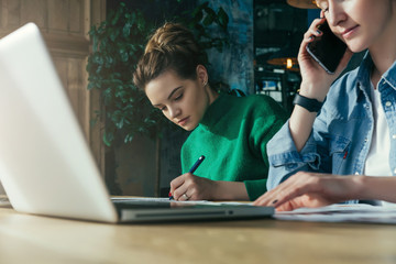 Close up.Two young business women sitting in office at table and work together.On table laptop and paper charts.First woman signs documents,second using talking on phone. Students learning online.