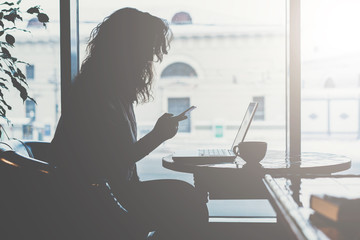 Side view.Early morning,silhouette of young woman with disheveled hair sitting at table in front of window and uses your smartphone.On table laptop and a cup of coffee. Businesswoman working online.