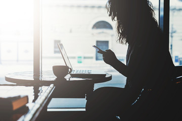 Side view.Early morning,silhouette of young woman with disheveled hair sitting at table in front of window and uses your smartphone.On table laptop and a cup of coffee. Freelancer working online.