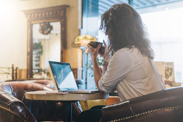 Rear view of young businesswoman in white shirt sits at round table in cafe,drinking coffee and using laptop. Girl shopping online, blogging, checking email. Student learning online.Freelancer working
