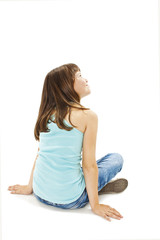 Rear view of little girl sitting on floor. Isolated on white background