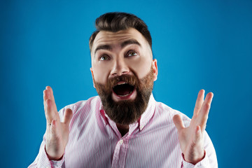 man with a beard in a pink shirt on a blue background shouting emotsianalno hands up  and yelling, screaming