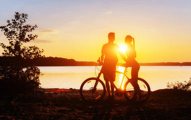 couple on a bicycle at sunset by the lake
