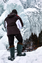 Landscape photographer at frozen waterfall