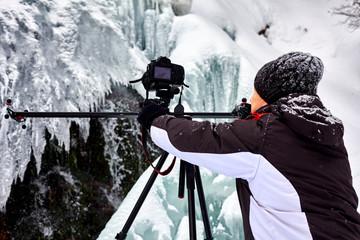 Landscape photographer at frozen waterfall