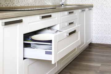 Fototapeta Opened kitchen drawer with plates inside, a smart solution for kitchen storage and organizing.  obraz