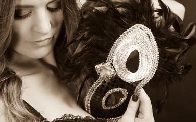 Sensual lady holding carnival mask.
