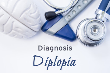 Diagnosis of Diplopia. Anatomical brain figure, neurological hammer and stethoscope lying on sheet of paper or book with the title neurological diagnosis of Diplopia. Concept for neurology