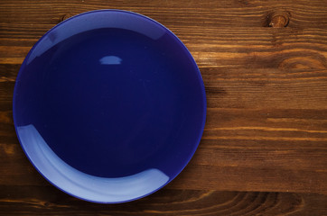 plate on a wooden background. blue  plate. plate top view. cop
