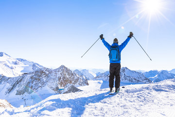 Back view of a happy skier with raised hands