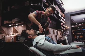 Barber applying cream on clients beard