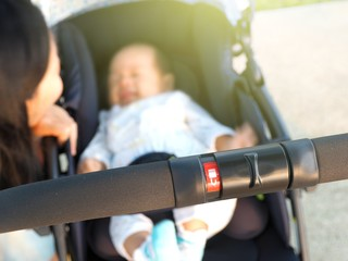 Lock folding stroller with baby and mother in the background. Concept of safety baby.