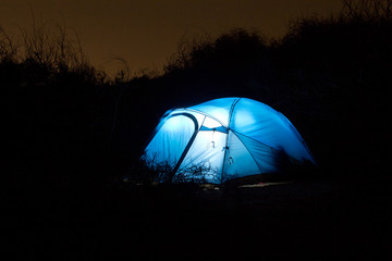 A tent glows under a night sky
