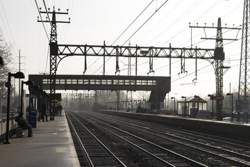 footbridge and pylons silhouetted at train station