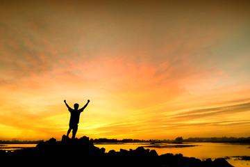 silhouette man Happy celebrating winning success at sunset