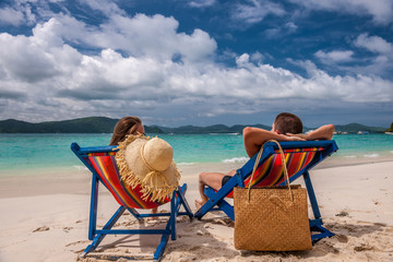 Couple on tropical beach in loungers