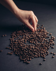 coffee grains on a gray background, hand
