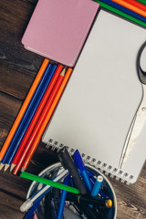 colorful pencils and a business card, a notebook and scissors on the table