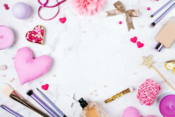 Frame with Hearts and makeup cosmetics, brushes and other essentials on white background top view. Beauty flat lay concept in pink and violet colors