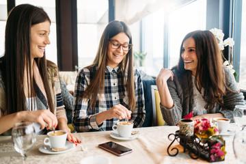 Three smiling women enjoy coffee talk at cafe