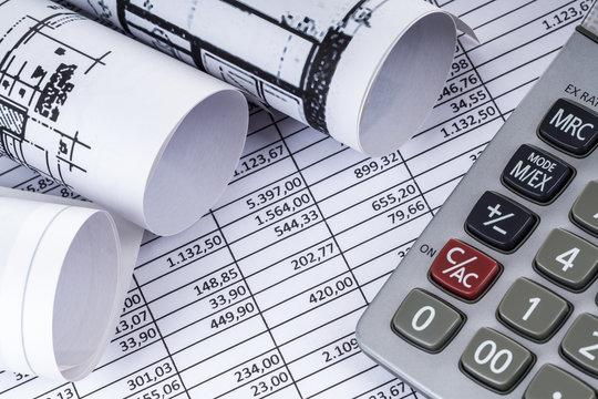 Taschenrechner und Baupläne auf einer Tabelle