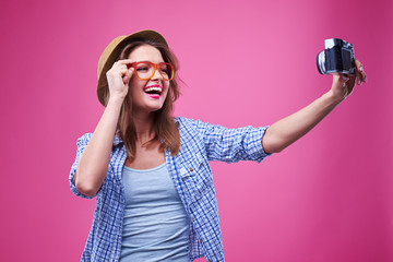 Funny youth wearing orange glasses and making a selfie photo