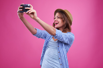 Trendy young woman making selfie with a silver retro camera