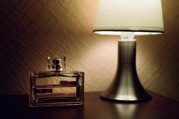 Table top lamp with burlap shade lit on a wooden table and a bottle of male perfume.