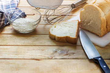 Place the bread on a white cutting board next to a knife on  woo