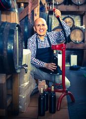 Cheerful mature man working on cork bottle device