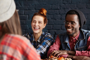 People, friendship and leisure concept. Happy interracial couple having fun at modern coffee shop, talking to their female friend and laughing cheerfully, enjoying lively and easy conversation