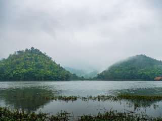 Beautiful tranquil lake and mountain covered with fog