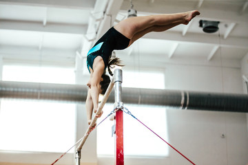 girl athlete gymnast exercises on uneven bars