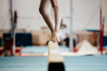 Foto auf Leinwand Gymnastik competition gymnastics exercises on balance beam girl gymnast