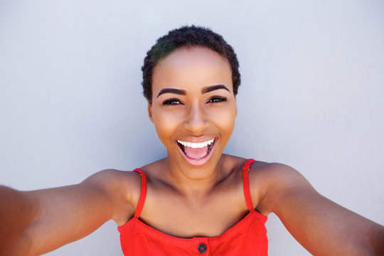 beautiful young black woman smiling and taking selfie